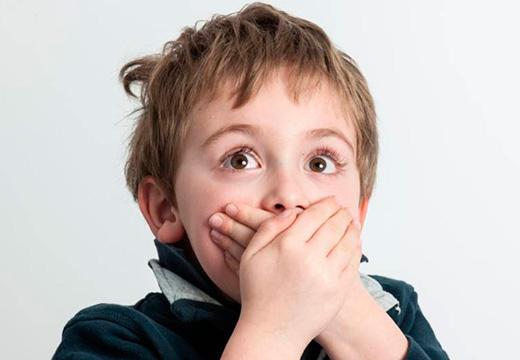 мальчик прикрывает рот