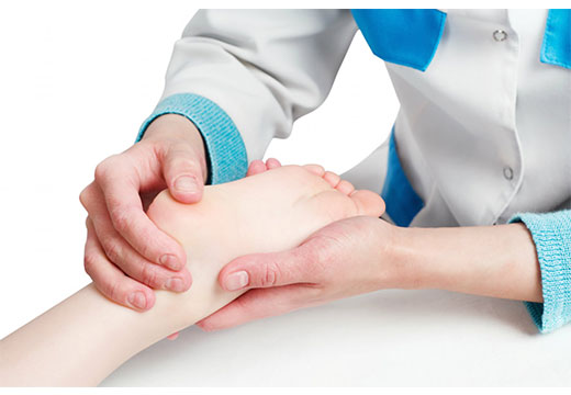 врач осматривает бородавку на ноге