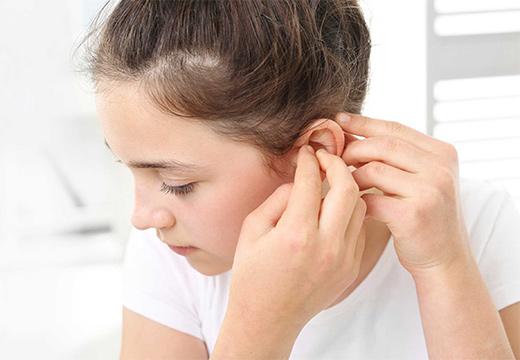 девочка трогает ухо