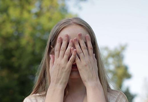 девушка прикрыла лицо руками