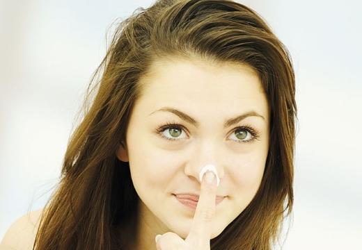девушка мажет нос кремом