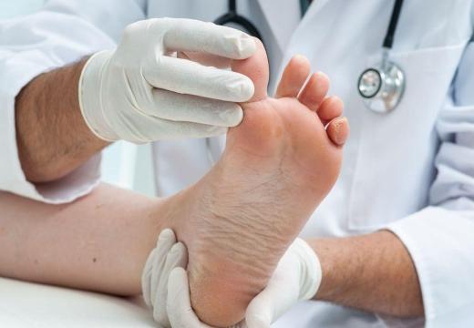 врач осматривает палец ноги